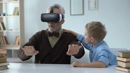 unokája : Grandpa wearing vr headset, delighted with new technologies, leisure with kid
