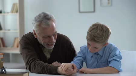 easily : Boy easily defeating grandfather in arm wrestling happy with victory, family fun Stock Footage