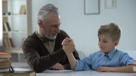 easily : Grandpa winning in arm wrestling with grandson, proud of kid, family leisure