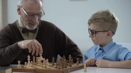 peão : Smart child playing chess with grandfather, family having fun, early development