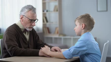 significado : Supportive kid stroking grandpas hand, family going through hard times together Stock Footage