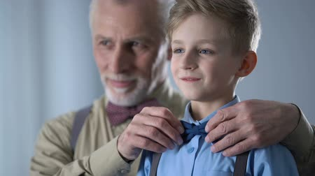 heir : Grandfather adjusting grandsons bow tie, preparing for performance, family care.