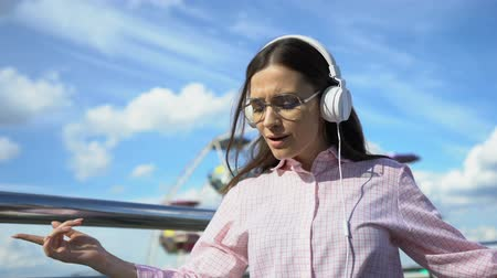 escuta : Positive brunette woman in headphones dancing and singing on pier, successful
