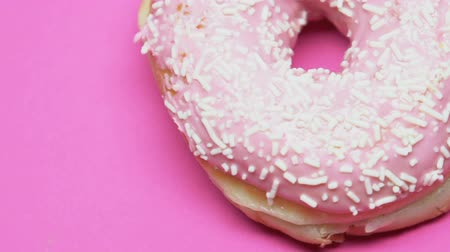 glikoz : Donut on spinning pink table, excess of sugar, diabetes, sweet dessert closeup Stok Video