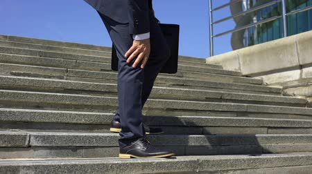 inflamed : Businessman going down stairs feeling strong knee pain, joint inflammation Stock Footage
