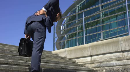 sedentary : Manager in suit suffering from lower back pain, slipped disc, disease symptom