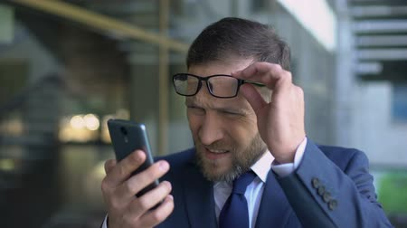 wzrok : Manager in eyeglasses trying read smartphone message, poor eyesight, health care