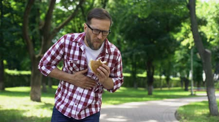 fájdalmas : Male eating burger walking, feeling sudden abdominal pain, unhealthy junk food Stock mozgókép