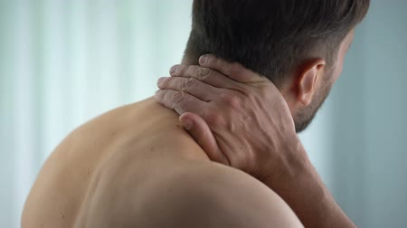 debilidad : Male touching neck, feeling strong spasm upper back, pinched nerve, discomfort