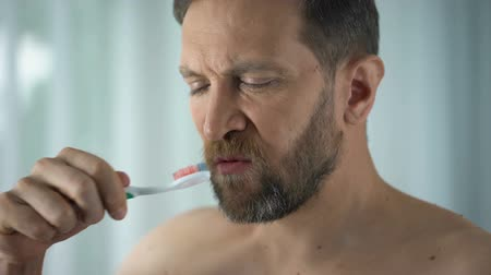 камедь : Caucasian man brushing teeth and seeing blood on toothbrush, dental care.
