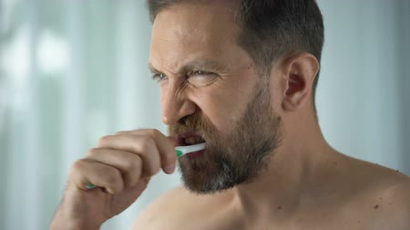 gengiva : Male in bathroom looking at blood toothbrush, oral hygiene, parodontosis illness