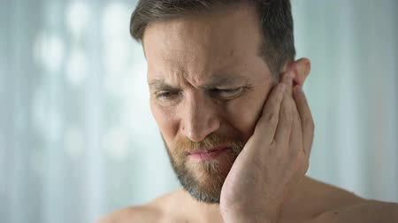 ear infection : Sick guy feeling ear pain, health care, neurological infection, itchiness otitis
