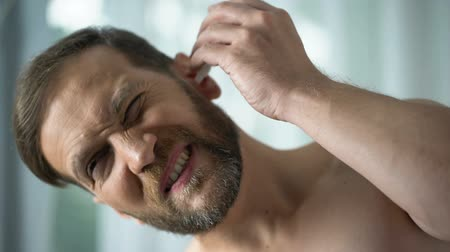 self injury : Unhealthy male dripping ear drops, bacterial infection self-treatment. Stock Footage