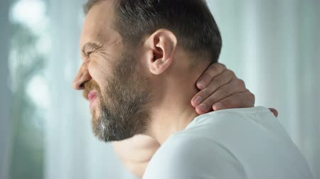 cramps : Caucasian male massaging neck, feeling discomfort, spinal problem, body care Stock Footage