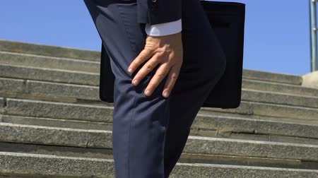 the inflammation : Male businessman feeling knee pain, walking downstairs, joint injury, close-up