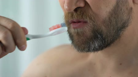 プラーク : Bearded man feels tooth pain while cleaning teeth, showing toothbrush with blood 動画素材