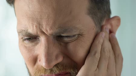 ear infection : Man disturbed by painful stuffiness in ear infection or inflammation.