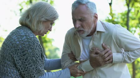 coronary : Retired couple walking in park, male pensioner suffering from heart attack