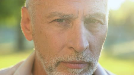 kapatmak : Bearded man in his 70s thinking about future and looking into camera, closeup
