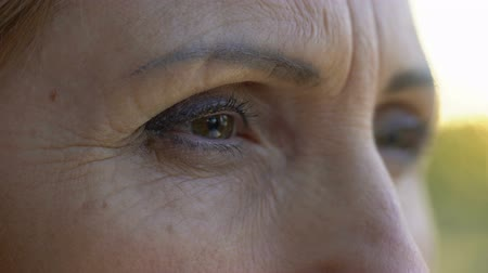 smutny : Extreme close-up of mature woman eyes, sad retired lady looking into camera
