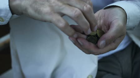 cent : Trembling hand of pensioner counting cent coins, victim of financial crisis Stock Footage