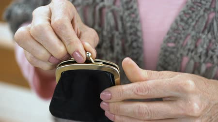 cent : Senior female hand putting cent coin in wallet, budget and money saving, closeup