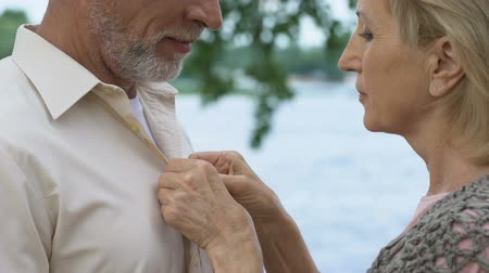 érettség : Mature man looking with love and tenderness, caring woman buttoning his shirt