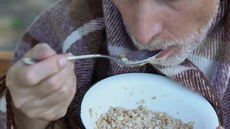 wrapped up : Old grandfather slowly eating porridge, charity meals for poor pensioners