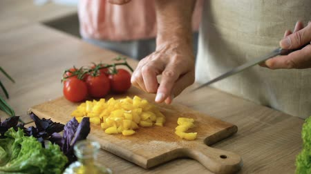 работа по дому : Senior man cutting yellow pepper and holding wife hands, household chores.