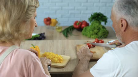 treating : Elderly married couple cutting vegetables in kitchen, cooking dinner together Stock Footage