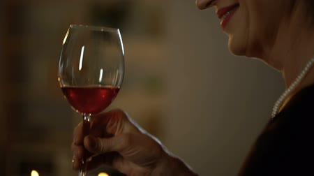 requintado : Elegant aged lady toasting and drinking red wine, romantic date in restaurant
