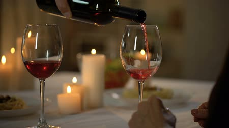 requintado : Caring husband pouring wine in wifes glass, couple having dinner together