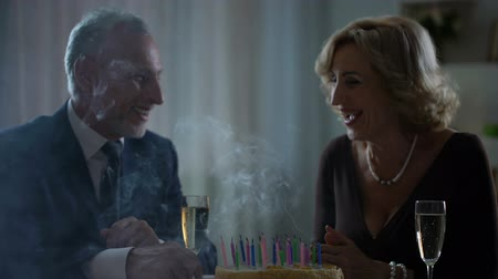 pezsgő : Elderly wife blowing cake candles, drinking champagne with husband, tradition
