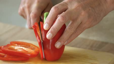 резать : Husband slicing pepper, man supports wife on diet, healthy organic food, closeup