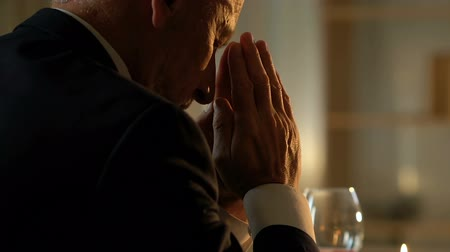 požehnat : Senior man praying at table before festive dinner, remembering passed away wife
