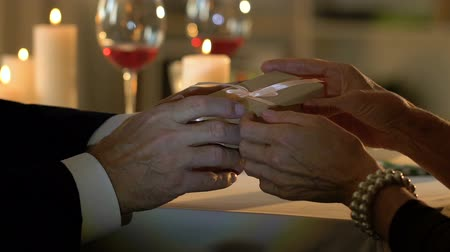 caring : Senior man giving present to woman on romantic date, marriage anniversary