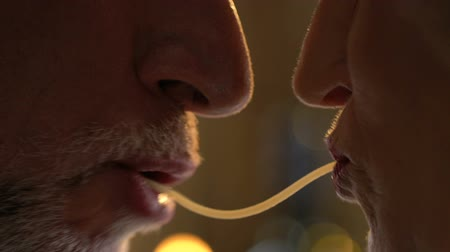 relação : Spaghetti kiss of senior couple, passion in spite of years.