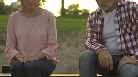 resentment : Senior couple sitting apart on bench outdoors, deception, breakup and resentment