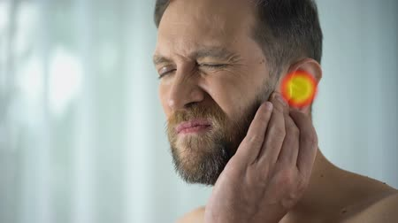 ear infection : Man suffers from earache, otitis, hearing problems, spot indicates pain, closeup
