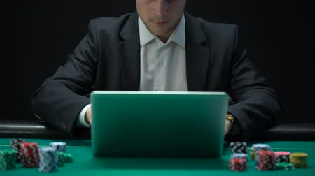 покер : Gambler playing on laptop and showing success gesture, winning bet, fortune