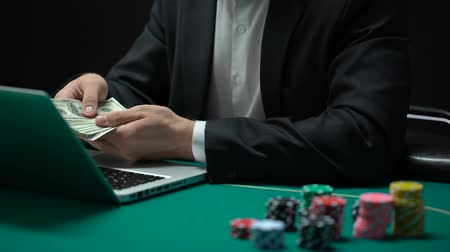 játékpénz : Online casino player counting dollars putting in prize money in pocket, gambling Stock mozgókép