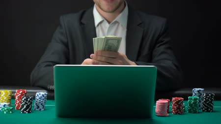 pontão : Successful online casino player counting money in front of laptop, bet winner