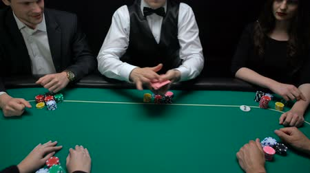 croupier : Casino dealer shuffling and distributing cards, players checking combination