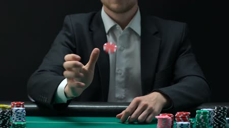 chips : Man in business suit tossing chips to make decision about bets gambling.