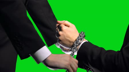 прикован : Business sanctions, chained arms on green screen background, economic conflict