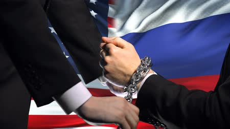строгий : United States sanctions Russia, chained arms, political or economic conflict.