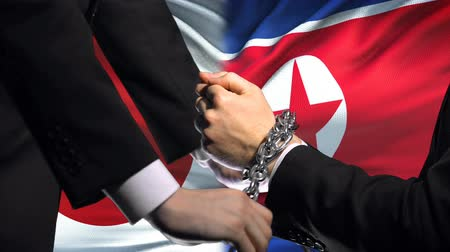прикован : Japan sanctions North Korea, chained arms, political or economic conflict