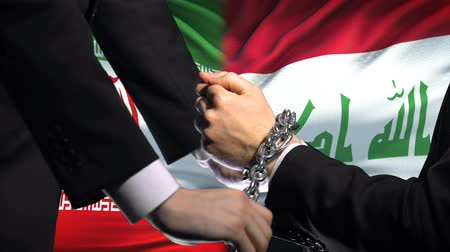 прикован : Iran sanctions Iraq, chained arms, political or economic conflict.