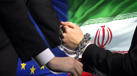 прикован : European Union sanctions Iran, chained arms, political or economic conflict.