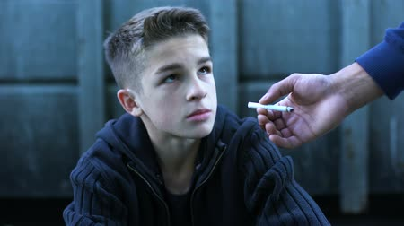 insurgent : Boy learning to smoke with older friend, bad influence of street life, addiction